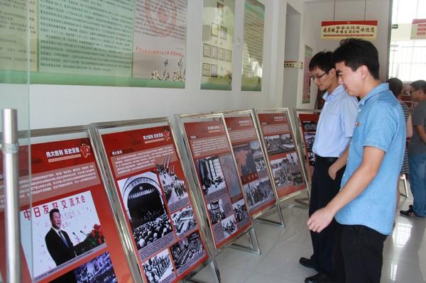 花岗镇团员青年在认真观看纪念抗战胜利70周年图片展