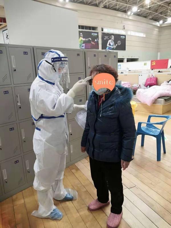 支援武汉护士张艳在方舱医院为患者量体温。拍摄者张成元,拍摄时间2月20日。.jpg