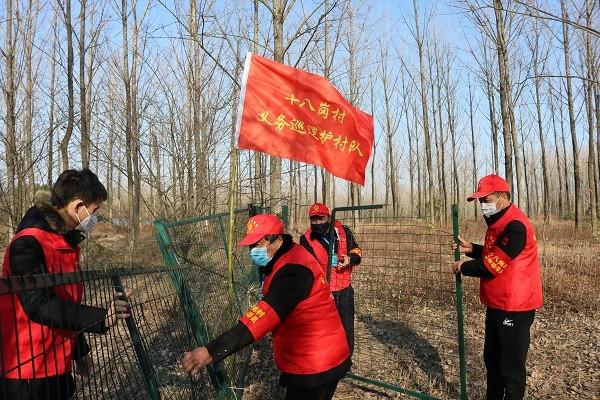 图4:十八岗村义务巡逻护村队在修补水源地隔离网。.JPG